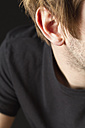Ear of young man with stubble against black background, close up - MBEF000110