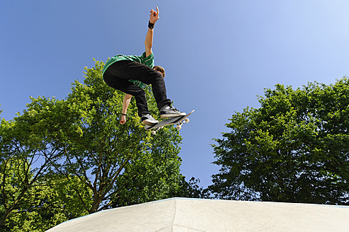 Germany, Duesseldorf, Young man performing tricks with skateboard in skatepark - KJF000106
