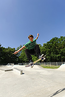 Germany, Duesseldorf, Young man performing tricks with skateboard in skatepark - KJF000104