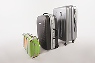 Variety of suitcases and luggages in a row against white background - WESTF016721