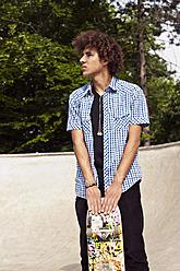 Germany, NRW, Duesseldorf, Man holding skateboard at public skatepark - KJF000111