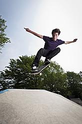Germany, NRW, Duesseldorf, Man skateboarding at public skatepark - KJF000116