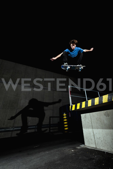 Germany, North Rhine-Westphalia, Duesseldorf, View of young skateboarder performing stunt at night - KJF000117