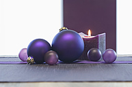 Close up of christmas bauble and candle on table - ASF004359