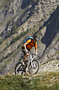 Italy, Livigno, View of man riding mountain bike near mountain - FFF001164