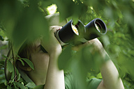 Germany, Bavaria, Close up of boy looking through binocular in forest - TCF001547