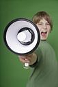 Boy screaming in megaphone against green background - TCF001555