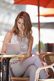 Germany, Lower-Bavaria, Landshut, Young woman sitting at street cafe with digital tablet - MAEF003374