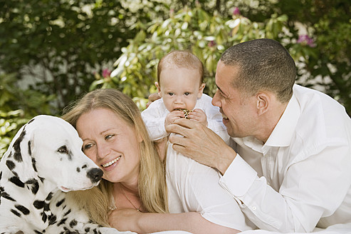 Germany, Bavaria, Father, mother and daughter with dalmatian in garden, smiling - RNF000620