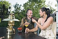Germany, Bavaria, Couple enjoying drinks with lantern in foreground - RNF000642