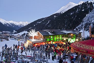 Austria, Tyrol, St. Anton am Arlberg, Mooserwirt, People skiing near ski hut in winter at dusk - WD000966