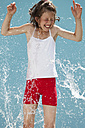 Germany, Girl jumping in splash of water against blue background - MAEF003419