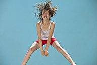 Germany, Girl jumping against blue background - MAEF003420