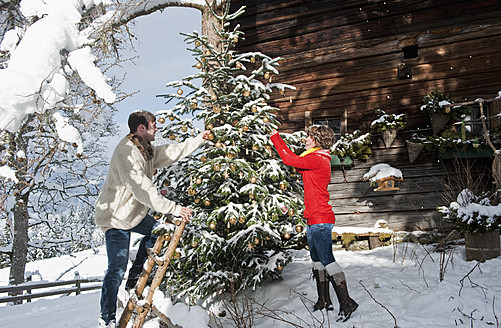 Austria, Salzburg Country, Flachau, Young man and woman decorating christmas tree in winter - HHF003672