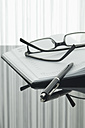Close up of notebook, pen and spectacles with reflection on table - ASF004375