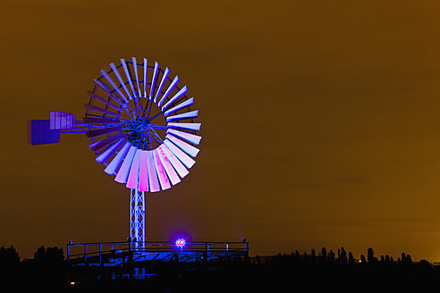 Germany, Nordrhein-Westfalen, Duisburg, Duisburg-Nord Landscape Park, View of illuminated wind mill of industrial plant at night - FOF003424