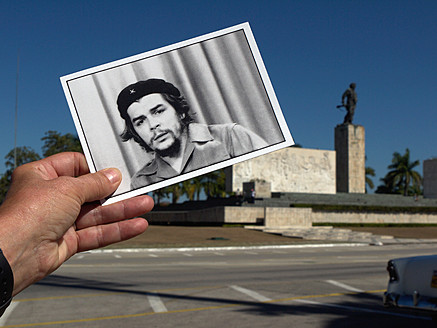 Cuba, Santa Clara, Close up of hand holding Che Guevara postcard with Memorial del Ernesto Che Guevara in background - BSC000044