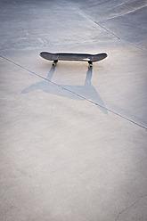Belgium, Mechelen, Skateboard lying on ground in public skatepark - KJF000126
