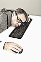 Close up of mature businessman lying on keyboard at office - MAEF003446