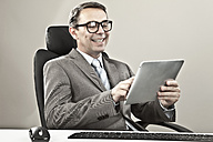 Businessman holding tablet pc and smiling against grey background - MAEF003458