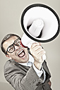 Close up of businessman screaming through megaphone against grey background - MAEF003468