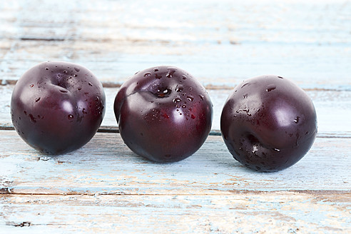 Three plums on wooden table, close up - MAEF003507