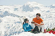 Austria, Salzburg Country, Altenmarkt-Zauchensee, Mid adult couple sitting and leaning on skis in winter snow - HHF003755