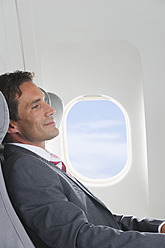 Germany, Bavaria, Munich, Mid adult businessman relaxing in business class airplane cabin - WESTF016791