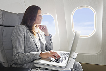Germany, Bavaria, Munich, Mid adult businesswoman using laptop in business class airplane cabin - WESTF016800