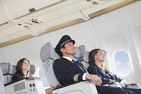 Germany, Bavaria, Munich, Mid adult flight personnels and stewardess resting in business class airplane cabin - WESTF016811