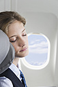 Germany, Bavaria, Munich, Close up of young stewardess sleeping in business class airplane cabin - WESTF016816