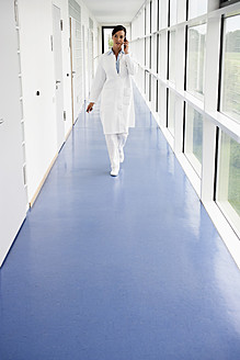 Germany, Bavaria, Diessen am Ammersee, Young doctor talking on mobile phone in corridor - JRF000244
