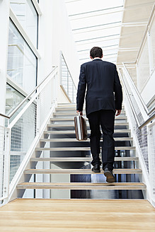 Germany, Bavaria, Diessen am Ammersee, Businesssman walking on staircase with briefcase - JRF000262