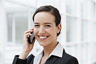 Germany, Bavaria, Diessen am Ammersee, Young businesswoman talking on mobile phone, smiling, portrait - JRF000282