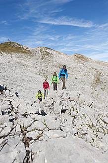 Austria, Kleinwalsertal, Group of people hiking on rocky mountain trail - MIRF000219