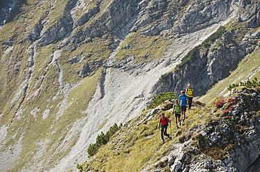 Austria, Kleinwalsertal, Group of people hiking on rocky mountain trail - MIRF000222