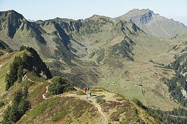 Austria, Kleinwalsertal, Group of people hiking on mountain trail - MIRF000225