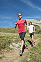 Austria, Kleinwalsertal, Man and woman running on mountain trail - MIRF000231