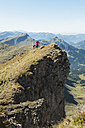 Austria, Kleinwalsertal, Man and woman trail running on mountain cliff - MIRF000237