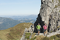 Austria, Kleinwalsertal, Man and woman hiking near rocks on mountain - MIRF000240