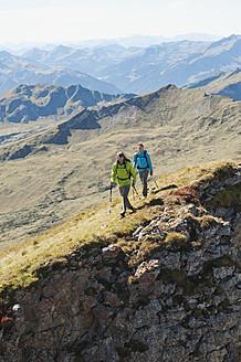 Austria, Kleinwalsertal, Man and woman hiking on edge of cliff - MIRF000243