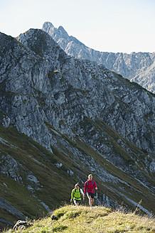 Austria, Kleinwalsertal, Man and woman hiking on mountain trail - MIRF000246