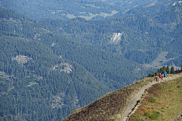 Austria, Kleinwalsertal, Man and woman hiking on mountain trail - MIRF000249