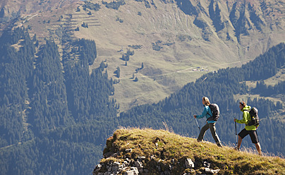 Austria, Kleinwalsertal, Man and woman hiking on edge of cliff - MIRF000252