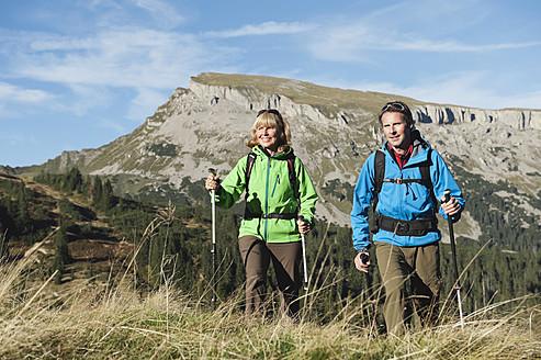 Austria, Kleinwalsertal, Man and woman hiking on mountain trail, smiling - MIRF000255