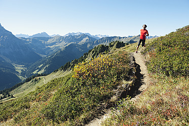 Austria, Kleinwalsertal, Mid adult man running on mountain trail - MIRF000258