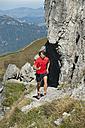 Austria, Kleinwalsertal, Mid adult man running on mountain trail near rocks - MIRF000264