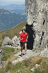 Austria, Kleinwalsertal, Mid adult man running on mountain trail near rocks - MIRF000264