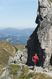 Austria, Kleinwalsertal, Young woman running on mountain trail near rocks - MIRF000273