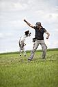 Germany, Lower Bavaria, Man training English Springer Spaniel in grass field - MAEF003531